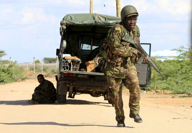 A Kenya Defense Force soldier runs for cover near the perimeter wall where attackers are holding up at a campus in Garissa April 2, 2015. At least 14 people were killed on Thursday when Islamist militant group al Shabaab stormed the Kenyan university campus, taking Christians hostage and engaging security forces in a shootout for several hours. (Photo by Noor Khamis/Reuters)
