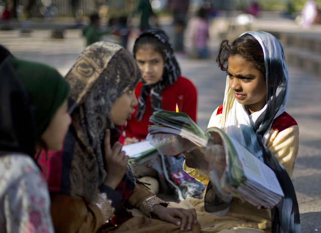 In this Thursday, March 12, 2015 photo, Pakistani children from slums study at a school set up by Mohammed Ayub, a 57-year-old government worker, at a park in Islamabad, Pakistan. Ayub has dedicated most of his life to teaching the less fortunate of this city. For three decades, children who might otherwise have gotten no education sat through his classes. (Photo by B. K. Bangash/AP Photo)