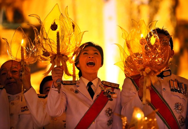 Thailand's Prime Minister Yingluck Shinawatra, center, along with other government and military officials hold candles and sing songs in honor of King Bhumibol Adulyadej during his birthday celebrations in Bangkok, on December 5, 2013. (Photo by Manish Swarup/Associated Press)