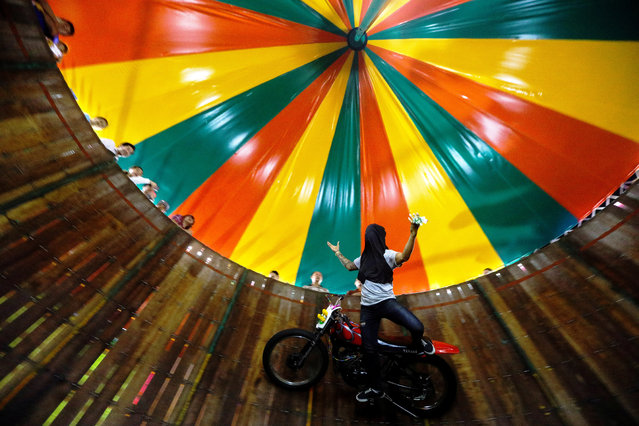A stuntman covering his face rides a motorcycle inside the Well of Death attraction during a fair in Bangkok, Thailand on November 27, 2018. (Photo by Athit Perawongmetha/Reuters)
