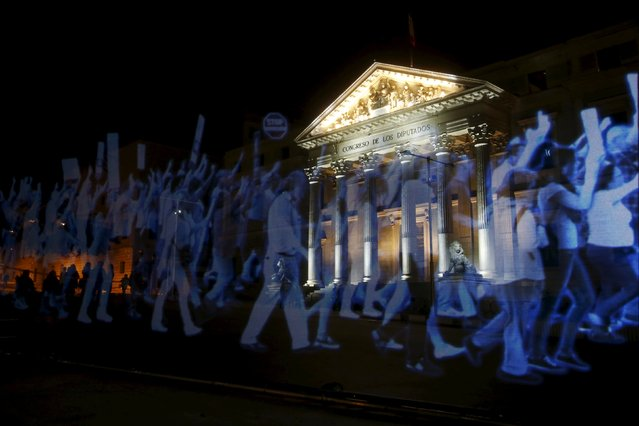 """A projection of images of people demonstrating is seen outside Spain's Parliament during a protest against the Spanish government's new security law in Madrid April 10, 2015. The new security law toughens fines for unauthorised street protests. Critics consider it a violation of the right to protest and a limit to free expression and have labelled it """"Ley Mordaza"""" (Gag Law). (Photo by Susana Vera/Reuters)"""