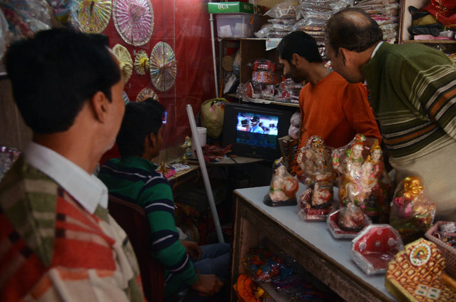 Indian shopkeepers watch the live broadcast of the Cricket World Cup match between Indian and Pakistan in Amritsar on February 15, 2015. (Photo by Narinder Nanu/AFP Photo)
