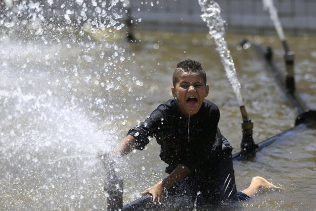 "An Egyptian child plays in a water fountain, during Sham el-Nessim, or ""smelling the breeze"", in Giza, Egypt, Monday, April 13, 2015. (Photo by Hassan Ammar/AP Photo)"