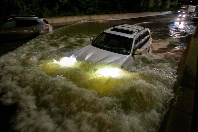 A motorist drives a car through a flooded expressway in Brooklyn, New York early on September 2, 2021, as flash flooding and record-breaking rainfall brought by the remnants of Storm Ida swept through the area. (Photo by Ed Jones/AFP Photo)