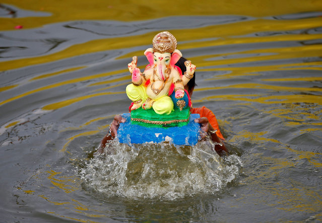 A boy immerses an idol of the Hindu god Ganesh, the deity of prosperity, into a pond on the second day of the ten-day long Ganesh Chaturthi festival in Ahmedabad, India, September 11, 2021. (Photo by Amit Dave/Reuters)