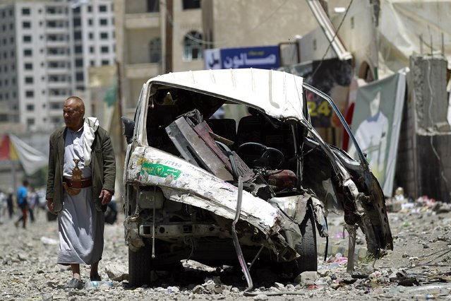 A Yemeni walks past a vehicle which was damaged the day before during an air strike by Saudi-led coalition warplanes on the nearby base on Fajj Attan hill on April 21, 2015 in the capital Sanaa. At least 38 civilians were killed in explosions that followed the air strike on the base on Fajj Attan hill that belongs to the missile brigade of the elite Republican Guard, which remains loyal to former president Ali Abdullah Saleh. (Photo by Mohammed Huwais/AFP Photo)