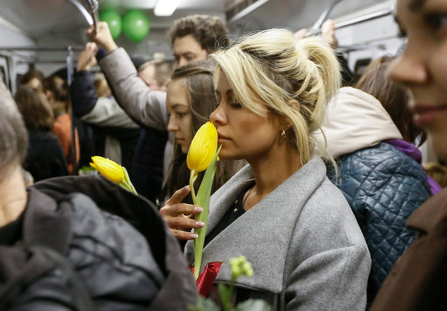 Female metro passengers hold flowers presented to them by metro workers, prior to International Women's Day in Kiev, Ukraine, 02 March 2016. (Photo by Sergey Dolzhenko/EPA)