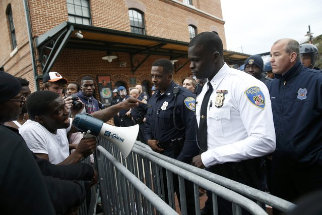 """Police stand guard outside Camden Yards as protesters gather for a rally to protest the death of Freddie Gray who died following an arrest in Baltimore, Maryland April 25, 2015. More than 1,000 demonstrators chanting """"shut it down"""" marched through Baltimore on Saturday to protest the death of a black man who died after being taken into police custody. (Photo by Shannon Stapleton/Reuters)"""