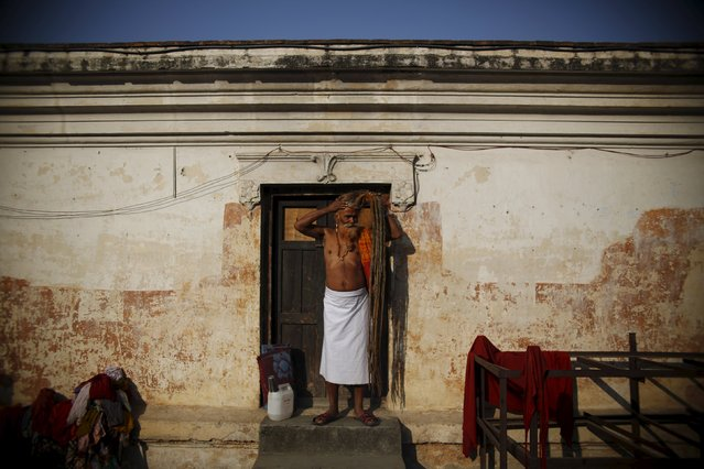 A Hindu holy man, or sadhu, ties his hair as he stands outside his ashram during the Shivaratri festival at the premises of Pashupatinath Temple in Kathmandu, Nepal, March 7, 2016. (Photo by Navesh Chitrakar/Reuters)