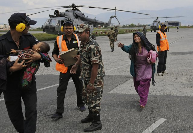 An Indian Air Force person walks carrying a Nepalese child, wounded in Saturday's earthquake, to a waiting ambulance as the mother rushes to join after they were evacuated from a remote area at the airport in Kathmandu, Nepal, Monday, April 27, 2015. (Photo by Altaf Qadri/AP Photo)