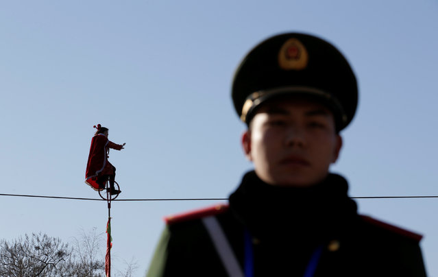 An acrobat rides a unicycle on tightrope during a temple fair celebrating the Chinese Lunar New Year at Daguanyuan park in Beijing, China January 30, 2017. (Photo by Jason Lee/Reuters)