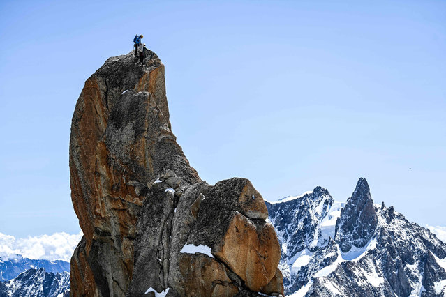Members of the Chamonix guides company take part in a special hike, between France and Italy near the Mont Blanc mountain, on July 10, 2021, to celebrate the 200th anniversary of the high mountain association . montain climing party in the world at l'aiguille du Midi the 10 july,2021 at Chamonix Mont Blanc. The company of Chamonix guides, the founding institution of mountaineering, celebrates its 200th anniversary on July 10, 2021 with the installation of a roped party of 200 people between the Aiguille du Midi and the Helbronner point, by the Italian border, above 3,000 m altitude, AFP journalists observed. (Photo by Olivier Chassignole/AFP Photo)