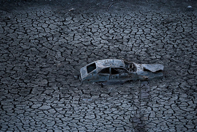A car sits in dried and cracked earth of what was the bottom of the Almaden Reservoir on January 28, 2014 in San Jose, California. Now in its third straight year of drought conditions, California is experiencing its driest year on record, dating back 119 years, and reservoirs throughout the state have low water levels. Santa Clara County reservoirs are at 3 percent of capacity or lower. (Photo by Justin Sullivan/Getty Images)
