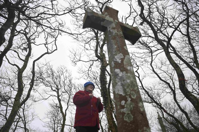 A woman prays at a stone cross during a Pattern Day pilgrimage to St. Brigid at the holy well of St. Brigid in Liscannor, Ireland, February 1, 2017. Located at a site of pre-Christian Lughnasadh celebrations, Dabhach Bhríde (or Brigid's Vat) is found near the Cliffs of Moher, and behind the well on a higher level, to which steps lead, is an ancient cemetery. There is a large cross here and a circular path around it, and part of the Rite of the Holy Well is performed in this area known as the Ula Uachtarach or upper sanctuary. The well, dedicated to Brigid of Kildare, is in the lower ground, the Ula íochtarach or lower sanctuary, enclosed in a little house full of votive offerings such as holy pictures, rosaries, medals and so forth left by pilgrims. Small items which people carry around with them, such as pens, biros and combs, are commonly found also as offerings at wells. The well has been the subject of a popular pilgrimage since at least the 1830s, when following a personal cure which he attributed to the waters of the well, Cornelius O'Brien had the well house built. Many pilgrims from all over County Clare and from the Aran Islands came to Liscannor. (Photo by Clodagh Kilcoyne/Reuters)