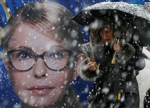 A woman passes by an election campaign tent of leader of opposition Batkivshchyna party and presidential candidate Yulia Tymoshenko, during snowfall in central Kiev, Ukraine on March 27, 2019. (Photo by Gleb Garanich/Reuters)