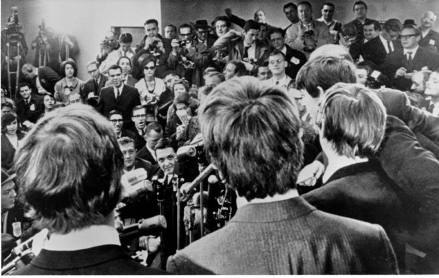 The Beatles face the media on arrival at JFK airport in New York City on February 7, 1964. The British rock and roll group was also greeted by a screaming crowd estimated at 5,000. (Photo by Charles Tasnadi/AP Photo)