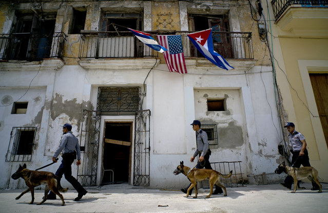Under a balcony decorated with Cuban and US flags, Cuban police arrive to the area where President Barack Obama will visit upon arrival in Old Havana, Cuba, Sunday, March 20, 2016. In his historic visit to Cuba, Obama is relegating decades of American acrimony with the communist country further into the past and cementing a new relationship between the Cold War-era foes. (Photo by Ramon Espinosa/AP Photo)
