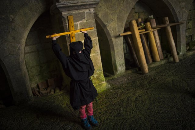 """A young masked penitents arrives with his cross to Roncesvalles Church during spring """"Romeria Cruceros de Arce"""", in Roncesvalles, northern Spain Sunday, May 10, 2015. (Photo by Alvaro Barrientos/AP Photo)"""
