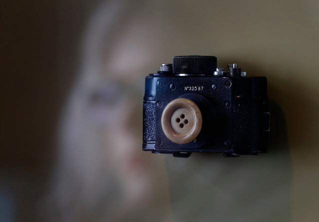 A woman is reflected in a glass box with a mini photo camera disguised under a button as part of the surveillance tactics employed by the former Ministry for State Security (Stasi) of the German Democratic Republic (GDR),on display at the Stasi Museum in Berlin, Germany, 21 February 2017. Stasi Museum since 1990 serves as a research and memorial centre investigating the political system of the former East Germany. 25 years ago the German Government ruled the declassification of the Stasi records and made them available to public access. Since then German citizens can request for possible surveillance files the Government of the GDR could gather about them. (Photo by Felipe Trueba/EPA)