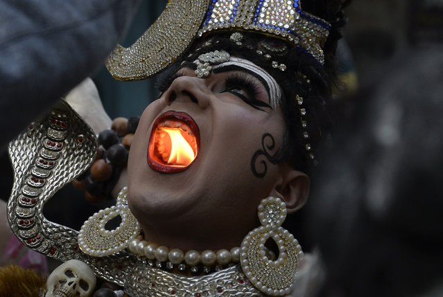 An Indian Hindu man dressed as Lord Shiva holds a lit candle in his mouth as he takes part in a religious procession ahead of the Maha Shivratri Festival in Jalandhar on February 22, 2017. Hindus mark the Maha Shivratri festival by offering special prayers and fasting to worship Lord Shiva, the lord of destruction. (Photo by Shammi Mehra/AFP Photo)