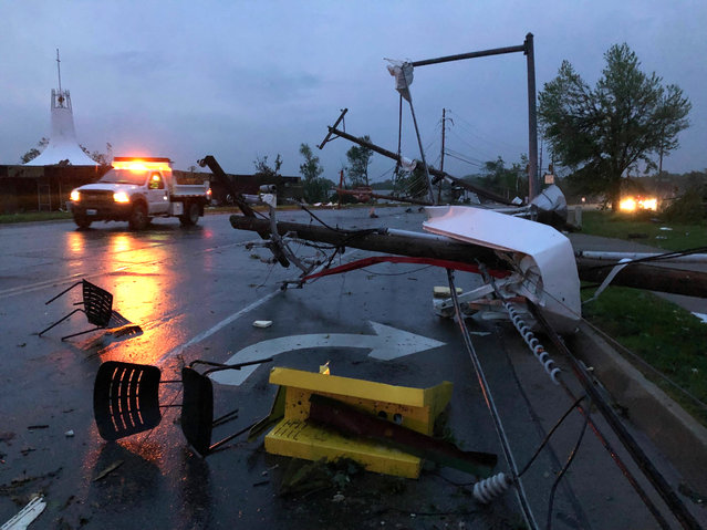 Plastic chairs lie in the road and metal from a damaged gas station roof is twisted around a downed power line in Jefferson City Missouri Thursday, May 23, 2019. The National Weather Service has confirmed a large and destructive tornado has touched down in Missouri's state capital, causing heavy damage and trapping multiple people in the wreckage of their homes. (Photo by David A. Lieb/AP Photo)