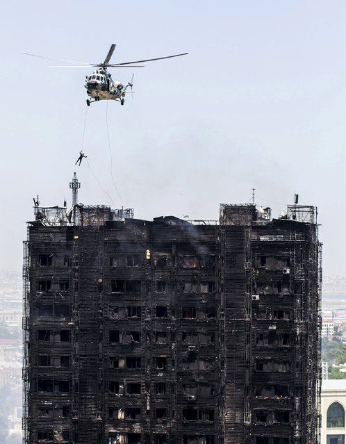 A rescuer descends from a helicopter over the roof of a burnt multi-storey residential building in Baku, Azerbaijan, May 19, 2015. (Photo by Ehtiram Jabi/Reuters)
