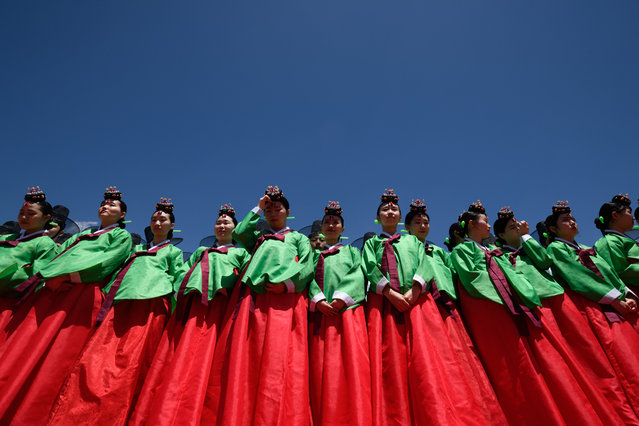 Young women wearing traditional hanbok dress line up for a group photo as they attend a traditional Coming-of-Age Day ceremony to mark adulthood at Namsan hanok village in Seoul on May 20, 2019. The ceremony marks the age of 19, at which a person is legally able to make life choices from voting, to drinking alcohol. (Photo by Ed Jones/AFP Photo)