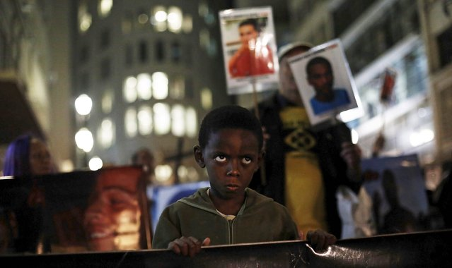 Joao Vitor, 7, looks next to demonstrators holding photographs of teens killed in shootings, as they protest against what they call police violence in Brazil, in downtown Sao Paulo May 15, 2015. (Photo by Nacho Doce/Reuters)