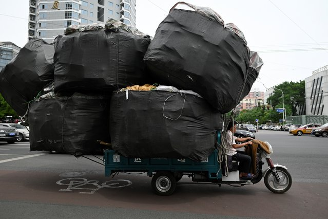 A man rides an electric tricycle loaded with goods on a street in Beijing on June 5, 2019. (Photo by Wang Zhao/AFP Photo)