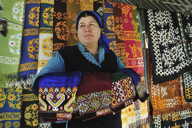 A woman looks out from her stall selling traditional garments and textiles at a market in Ashgabat February 8, 2012. (Photo by Aman Mehinli/Reuters)