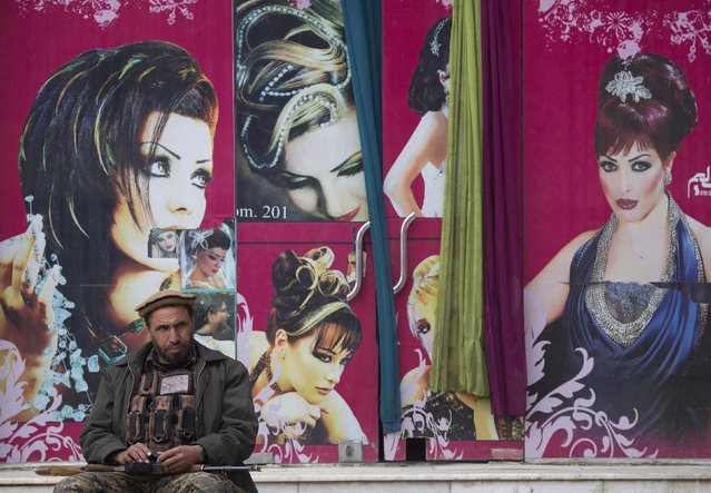 A security guard sits in front of a barber shop outside the Kabul-Dubai wedding hall in Kabul March 8, 2014. (Photo by Morteza Nikoubazl/Reuters)