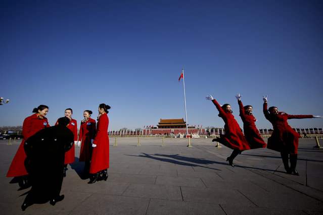 In this Sunday, March 5, 2017 photo, hospitality staff jump as they pose for photographs on Tiananmen Square during the National People's Congress held at the Great Hall of the People in Beijing. (Photo by Andy Wong/AP Photo)