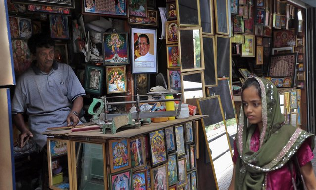 A Sri Lankan Muslim woman walks past a picture framing shop where a portrait of President Maithripala Sirisena is on display in Colombo, Sri Lanka, Saturday, June 27, 2015. Sirisena dissolved Parliament loyal to his predecessor and called fresh elections in August in an attempt to consolidate power and carry out his promise of reforms. (Photo by Eranga Jayawardena/AP Photo)