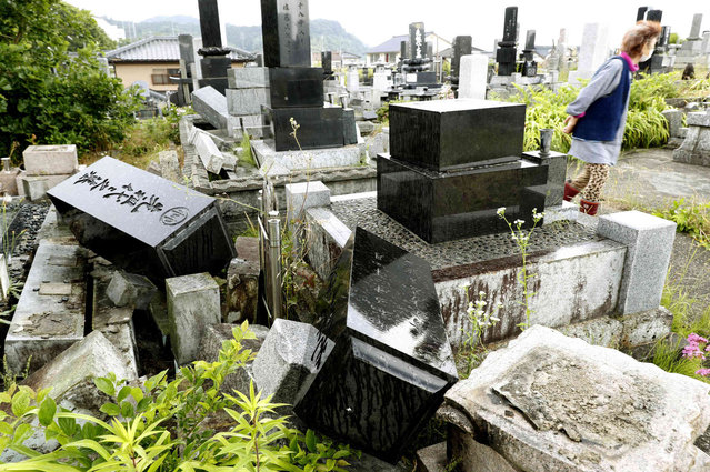 A woman walks past collapsed gravestones in Murakami, Niigata prefecture, northwestern Japan, Wednesday, June 19, 2019, after an earthquake. The powerful earthquake jolted northwestern Japan late Tuesday, prompting officials to issue a tsunami warning along the coast which was lifted about 2 ½ hours later. (Photo by Yusuke Ogata/Kyodo News via AP Photo)