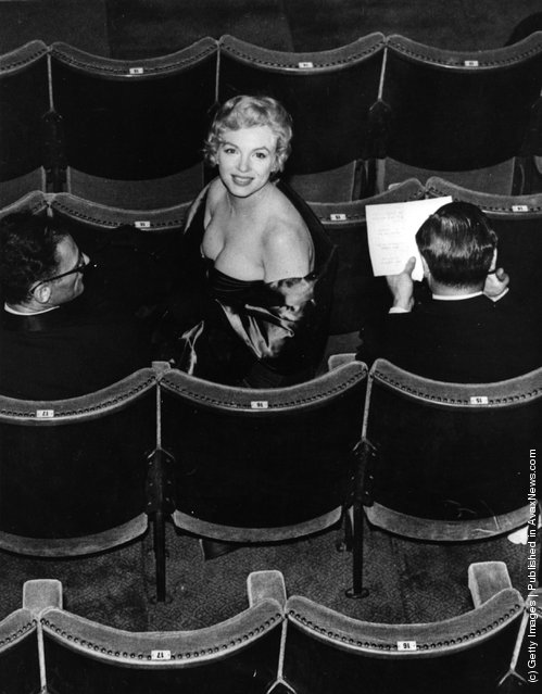 Marilyn Monroe (Norma Jean Mortenson or Norma Jean Baker, 1926 - 1962) takes her seat in the audience for a performance of the play 'A View From The Bridge', written by her husband Arthur Miller (left). The play is being performed at the Comedy Theatre in London