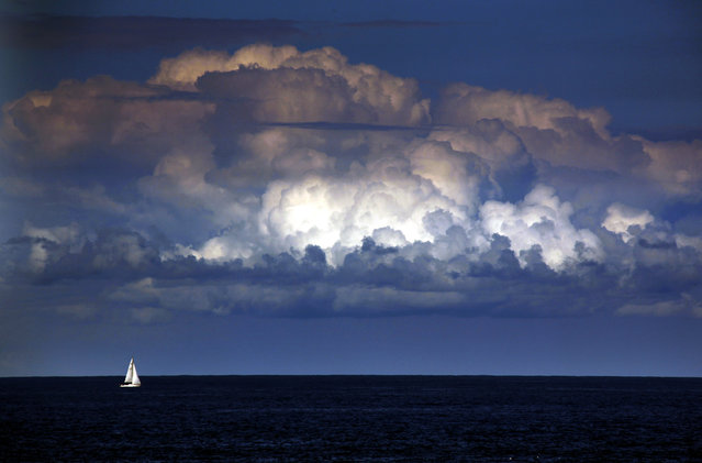 "A storm cloud can be seen behind a yacht as it sails off the coast of Sydney March 31, 2014. The Bureau of Meteorology last week forecast ""warmer and drier than usual"" weather extending well into winter for Sydney and most of south-eastern Australia over the next three months. (Photo by David Gray/Reuters)"