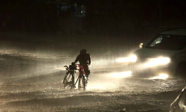 An Indian man walks with his cycle through a water-logged street as it rains in Jammu, India, Monday, June 29, 2015. Heavy rains lashed the city bringing much needed relief from the scorching heat wave. (Photo by Channi Anand/AP Photo)