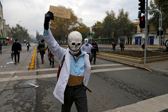 """A demonstrator holds up a sign that reads """"Luksic (A Chilean business man) Dies!"""" during a rally commemorating May Day in Santiago, Chile May 1, 2016. (Photo by Ivan Alvarado/Reuters)"""