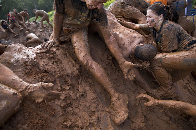 People take part in the Mud Day race, a 13 kilometer obstacle course in Tel Aviv, Israel, Friday, March 24, 2017. (Photo by Oded Balilty/AP Photo)