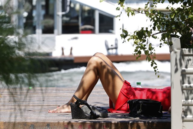A woman enjoys the sun along the banks of River Seine on a hot summer day in Paris, France, July 1, 2015. (Photo by Charles Platiau/Reuters)