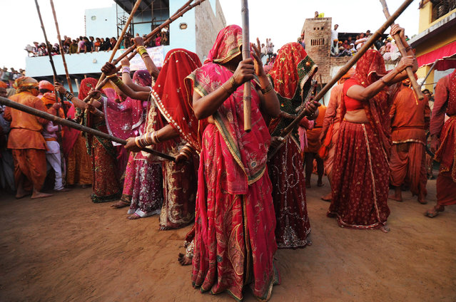 """""""Lathmar Holi"""". Women from Barsana village, home of Krishna's lover, Radha, come to Krishna's village, Nandgaon, during the Lathmar Holi celebrations. During Lathmar Holi, the women of Barsana beat the men from Nandgaon with wooden sticks in response to their teasing. The men use shields to protect themselves, all done in good humor. Photo location: Nandgaon, UP, India. (Photo and caption by Anirudha Chakraborty/National Geographic Photo Contest)"""