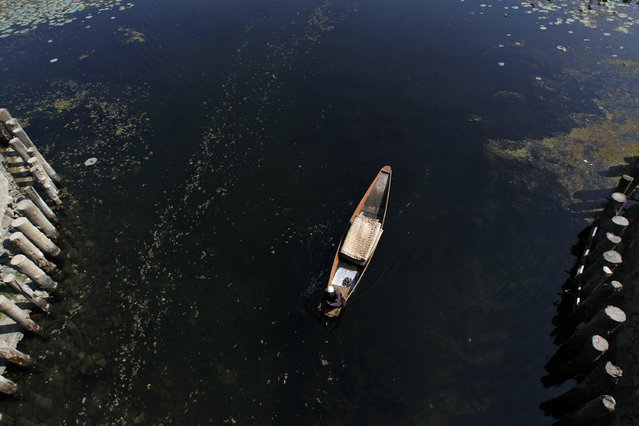 A Kashmiri boatman selling traditional floor mats rows his boat on the waters of Dal Lake in Srinagar October 15, 2011. (Photo by Fayaz Kabli/Reuters)