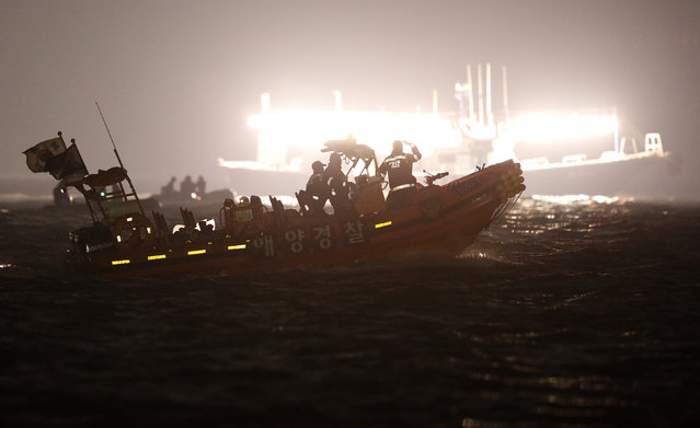 South Korean rescue workers operate where the capsized passenger ship Sewol sank, as fishing boats emit light during the night rescue operation in Jindo April 22, 2014. The Sewol ferry sank last Wednesday on a routine trip south from the port of Incheon to the traditional honeymoon island of Jeju. Of the 476 passengers and crew on board, 339 were children and teachers on a high school outing. (Photo by Issei Kato/Reuters)