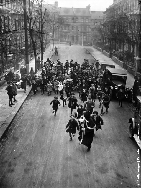 1926: A crowd of happy youngsters chase Father Christmas along a London street. He is on his way to a south London store to distribute presents