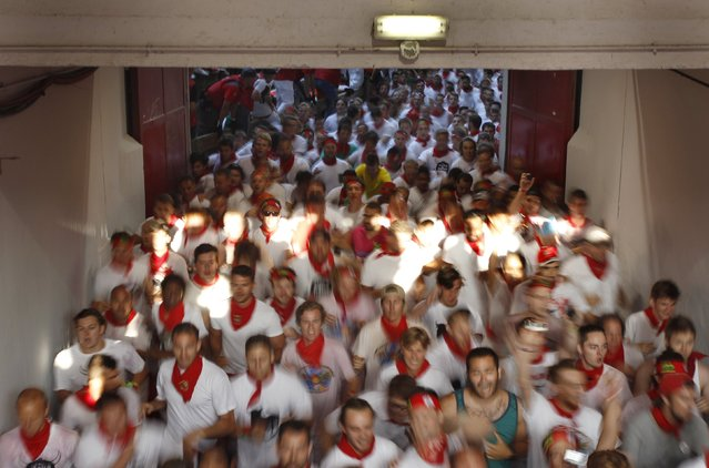 Runners sprint into the bullring during the first running of the bulls of the San Fermin festival in Pamplona, northern Spain, July 7, 2015. (Photo by Joseba Etxaburu/Reuters)