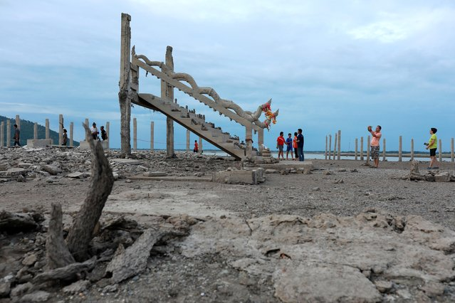 People walk and take pictures at the ruins of a Buddhist temple which has resurfaced in a dried-up dam due to drought, in Lopburi, Thailand on August 1, 2019. Thousands are flocking to see the Buddhist temple exposed after drought drove water levels to record lows in a dam reservoir where it had been submerged. (Photo by Soe Zeya Tun/Reuters)