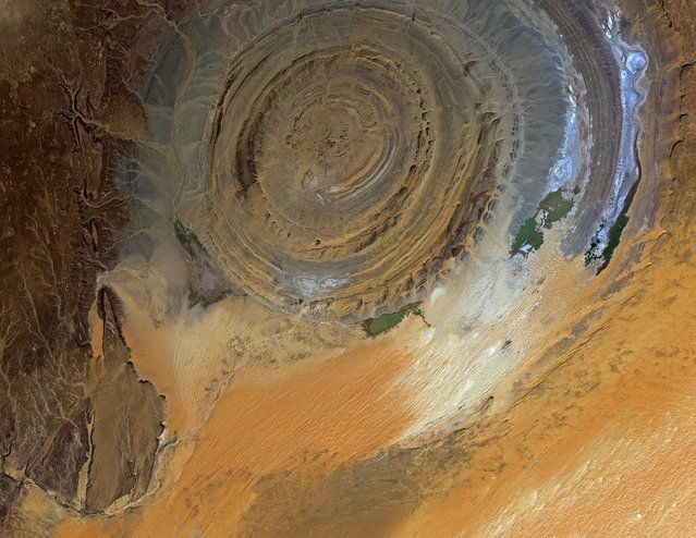 A handout picture released by ESA on 02 May 2014 and taken by Japan's ALOS satellite on 23 November 2010 shows the 40 km-diameter circular Richat structure in the Sahara desert of Mauritania, one of the geological features that is easier to observe from space than from down on the ground, and has been a familiar landmark to astronauts since the earliest missions. (Photo by EPA/Jaxa/European Space Agency)