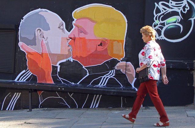 A woman walks past a mural on a restaurant wall depicting US  Presidential hopeful Donald Trump and Russian President Vladimir Putin greeting each other with a kiss in the Lithuanian capital Vilnius on May 13, 2016. Kestutis Girnius, associate professor of the Institute of International Relations and Political Science in Vilnius university, told AFP – This graffiti expresses the fear of some Lithuanians that Donald Trump is likely to kowtow to Vladimir Putin and be indifferent to Lithuanias security concerns. (Photo by Petras Malukas/AFP Photo)