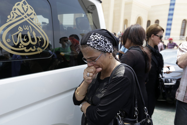 A woman mourns next to a car carrying the coffin of Egyptian actor Omar Sharif during his funeral procession at the Hussein Tantawi Mosque in Cairo, Egypt, Sunday, July 12, 2015. (Photo by Hassan Ammar/AP Photo)