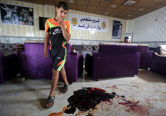 An Iraqi boy walks past the blood stains and debris at a cafe, that was popular with local fans of Spain's Real Madrid football club, in the Balad area, north of the capital Baghdad, on May 14, 2016, a day after a deadly raid claimed by Islamic State group militants. At least 16 people were killed and 30 wounded, including several members of the security forces, in the attack in the town of Balad and the ensuing chase, officials said. (Photo by Ahmad Al-Rubaye/AFP Photo)